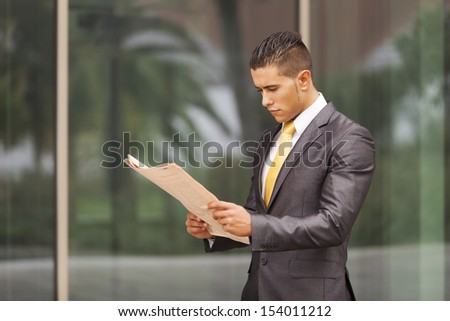 Businessman reading his newspaper next to his office building