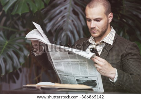 Businessman reading newspaper on chair at office building hall or cafe - stock photo