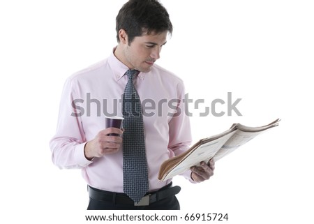 Businessman reading newspaper while holding a cup of coffee - stock photo