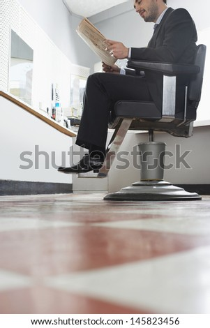 Businessman reading newspaper while waiting for haircut in hair salon - stock photo