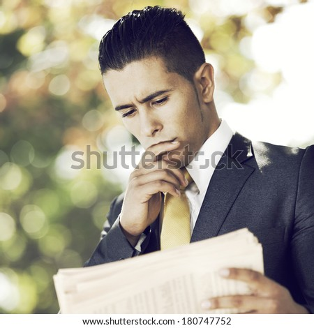 Businessman reading the newspaper at the city park - stock photo