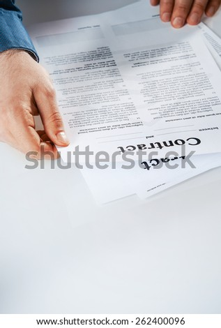 Businessman reading through a contract sitting at his desk checking the fine print before signing it, high angle view with copyspace - stock photo