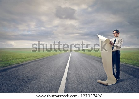businessman reads the paper roll on the road - stock photo