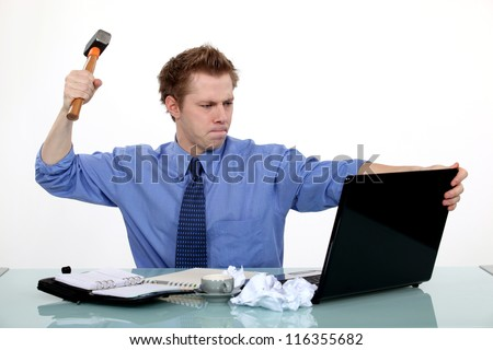 businessman ready to smash his laptop with a hammer - stock photo
