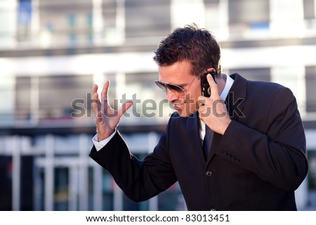 Businessman receiving bad news in front of an office building - stock photo