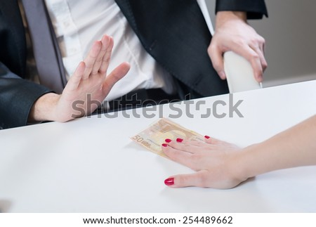 Businessman refusing the money offered by business woman in office, no corruption. - stock photo