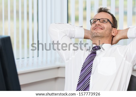 Businessman relaxing at his desk leaning back in his chair with his hands behind his head and a contented smile - stock photo