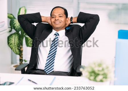 Businessman relaxing at the office with hands behind his head - stock photo