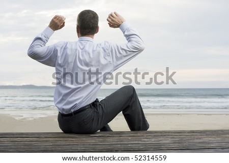 Businessman relaxing at the sea while sitting on a wooden platform - stock photo