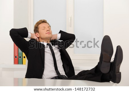 Businessman relaxing. Handsome young men in formalwear sitting at his working place and holding his head in hand