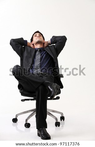Businessman relaxing in black chair - stock photo