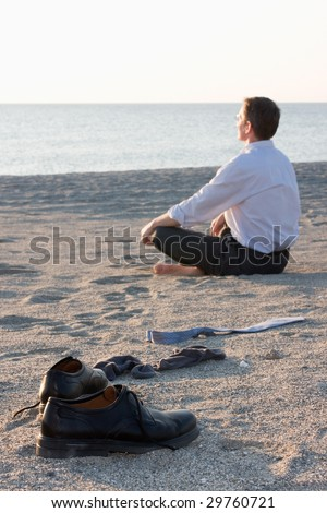 Businessman relaxing on beach - Focus on the shoes in the foreground - stock photo