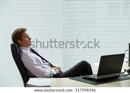 Businessman relaxing on chair with laptop on desk - stock photo