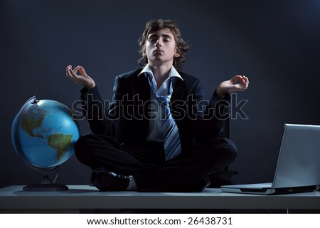 Businessman relaxing on desk in yoga lotus position - stock photo