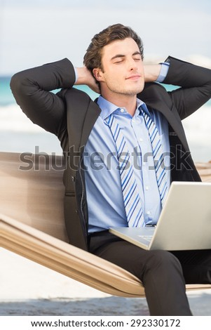 Businessman relaxing on hammock at the beach - stock photo