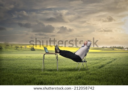 businessman relaxing while  sitting at his desk - stock photo