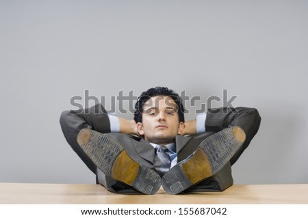 Businessman relaxing with his feet on desk