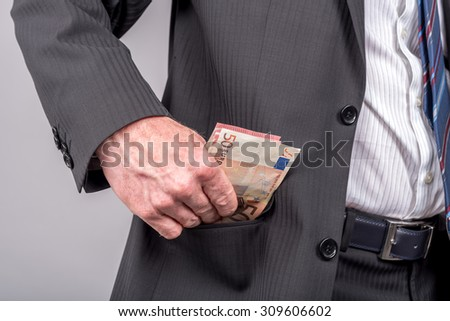Businessman removing euro banknotes from his pocket