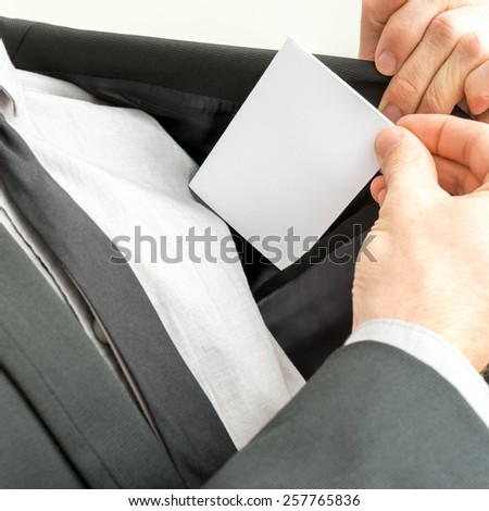 Businessman removing or placing a blank white business card in the inner pocket of his suit jacket, close up view of the card with copyspace. - stock photo