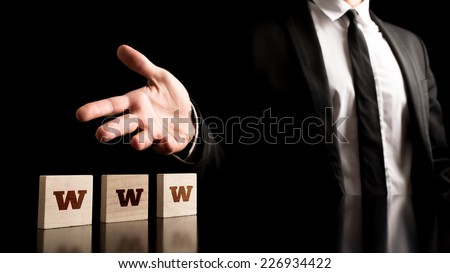 Businessman Representing Small Wooden Pieces with WWW Letters on Black Background. - stock photo