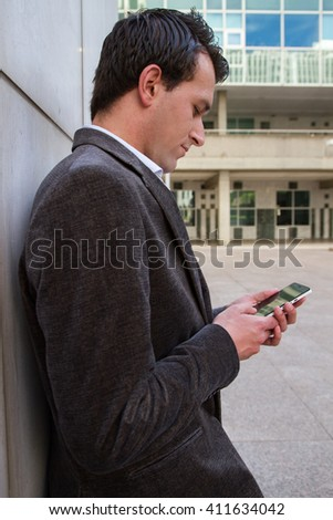 Businessman resting from work and while sending messages and talking with his smart phone.