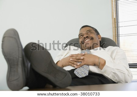 Businessman resting on a chair and smiling. - stock photo