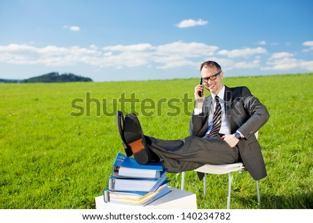 Businessman resting while calling through telephone in Greenfield