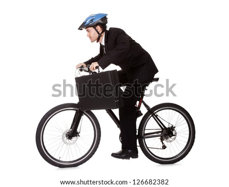 Businessman riding a bicycle to work in his suit exercising for fitness and health and to save on carbon emissions - stock photo