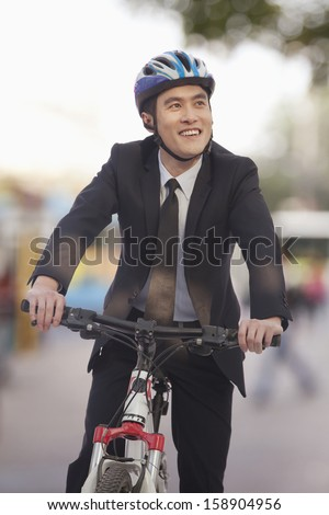 Businessman riding bicycle - stock photo