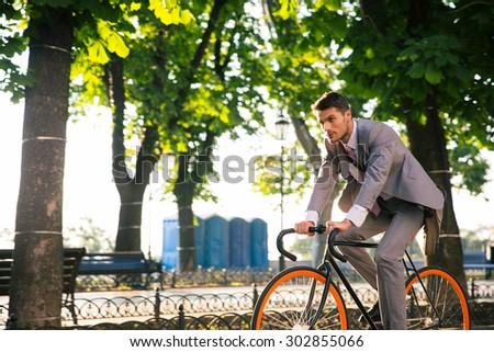 Businessman riding bicycle to work in park in morning - stock photo