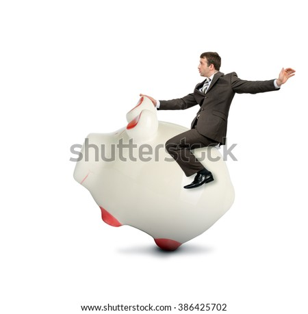 Businessman riding piggy bank