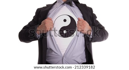 Businessman rips open his shirt to show his yin and yang t-shirt - stock photo
