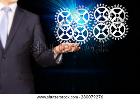 businessman rotates the gear mechanism with dents in the form of people walking - stock photo
