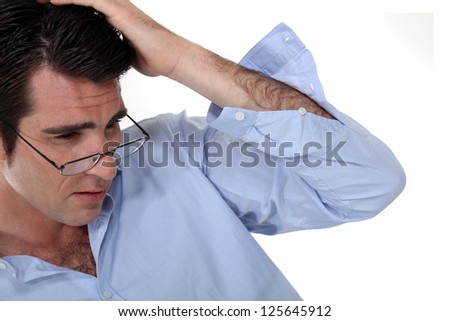 Businessman rubbing his head - stock photo