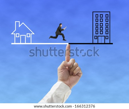 Businessman running on seesaw with Office and home, for index finger to balance  - stock photo