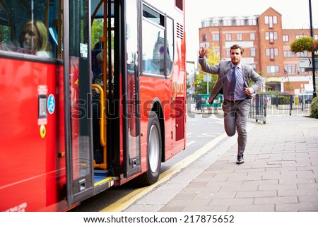 Businessman Running To Catch Bus Stop - stock photo