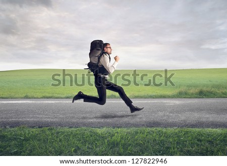 businessman running with backpack on the road - stock photo