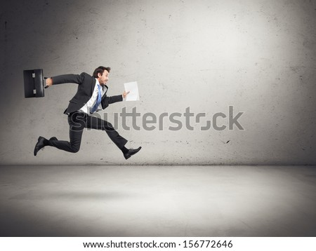 businessman running with papers and briefcase in his hands - stock photo