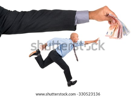 Businessman running with raised arms chasing money - stock photo