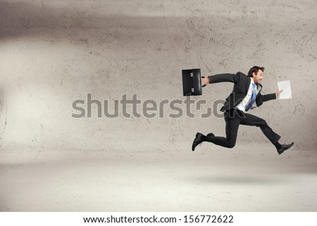businessman running with some documents in his hand - stock photo