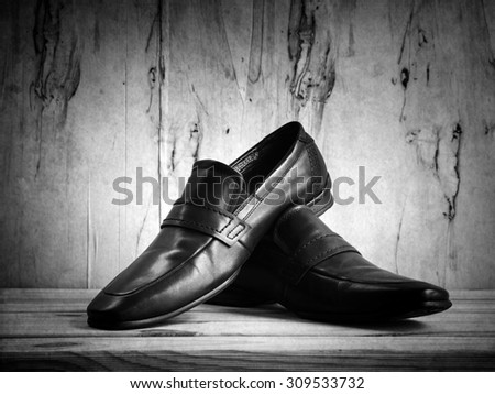 Businessman's accessories with shoes on wooden table over grunge background, black and white