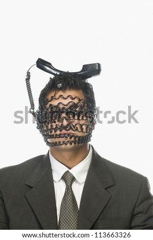 Businessman's face wrapped with telephone cord with it's receiver on his head - stock photo