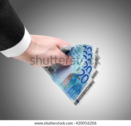 Businessman's hand holding a stack of twenty euro notes isolated on graduate background. - stock photo
