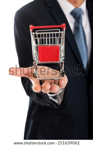 Businessman's hand holding small shopping cart