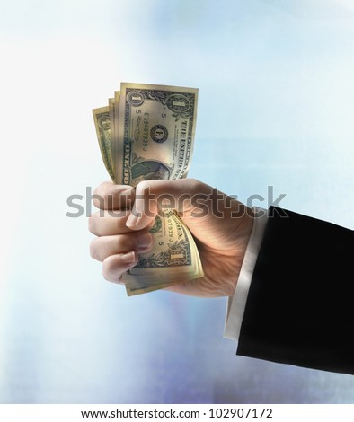 Businessman's hand holding US dollars - stock photo