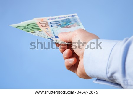 Businessman's hand reaching out euro banknotes, blue background