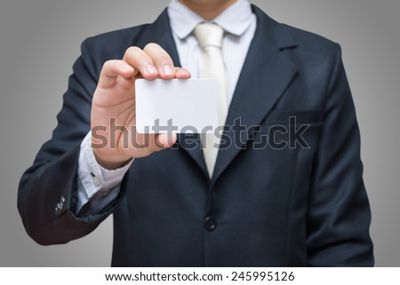 Businessman's hand showing business card on grey background - stock photo