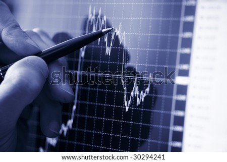 Businessman's hand showing diagram on financial report with pen - stock photo
