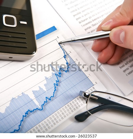 Businessman's hand showing diagram on financial report with pen. Business background 03