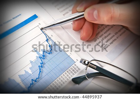Businessman's hand showing diagram on financial report with pen. Business background 02 - stock photo